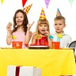 Croup of happy children celebrating birthday behind table — Stock Photo #43197919