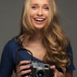 Positive young woman with long hair and blue eyes holding vintage style camera — Stock Photo #43198049
