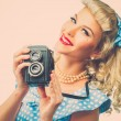 Blond coquette pin up style young woman in blue dress with vintage camera — Stock fotografie