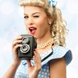 Blond coquette pin up style young woman in blue dress with vintage camera — Stock Photo #43198821