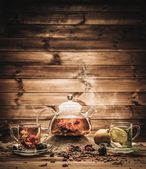 Teapot and glass cups with  tea against wooden background — Stock Photo