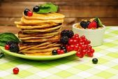 Healthy breakfast with pancakes, fresh berries and muesli on tablecloth in rural interior  — ストック写真