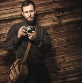 Handsome man wearing cardigan with vintage camera in wooden house interior  — ストック写真