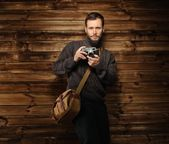 Handsome man wearing cardigan with vintage camera in wooden house interior  — Foto de Stock