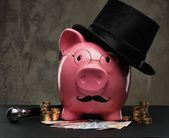 Piggybank in glasses and hat with pile of coins and banknotes — Stock Photo