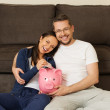 Cheerful young couple putting banknote in piggybank — Stock Photo #43665921
