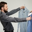 Handsome man with beard choosing shirt  — Stock Photo #43666315