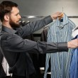 Handsome man with beard choosing shirt in a shop — Stock Photo
