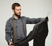 Handsome man with beard choosing jacket  — Stock Photo