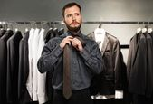 Handsome man with beard tying a tie in a clothing store — Stock Photo