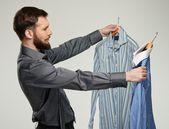 Handsome man with beard choosing shirt  — Stock Photo
