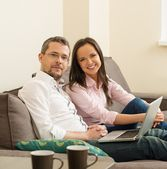 Young cheerful couple with laptop on a sofa in home interior  — Stock Photo