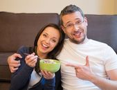 Funny young couple with bowl of muesli in home interior  — Stock Photo