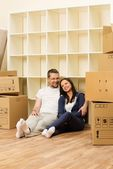 Young positive couple  among boxes in their new home — Stock Photo