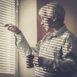 Senior man with cup looking out the window through jalousie  — Stock Photo #44582273