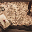 Compass, book and envelope on a vintage map — Stock Photo