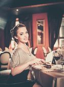 Beautiful young girl alone in a restaurant — Stock Photo