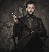 Handsome well-dressed with stick sitting in leather chair  — Stock Photo