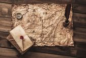 Compass, book and envelope on a vintage map — Stockfoto
