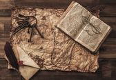 Bunch of old keys, book and envelope on a vintage map — Foto Stock