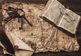 Bunch of old keys, book and envelope on a vintage map — Stock Photo