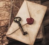 Old key and envelope on a vintage book — Stockfoto