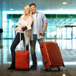 Happy couple with suitcases and map in airport — Stock Photo