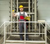 Funny worker in safety hat on a factory — Stock Photo