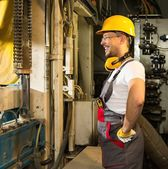 Cheerful worker in safety hat near machine on a factory — Stock Photo