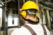 Worker in safety hat and headphones working behind machine on a factory — Stock Photo