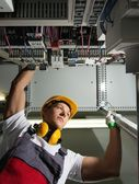 Electrician in a safety hat and headphones on a factory — Stock Photo