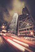 Fast moving cars at night in modern city — Stock Photo