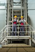 Two men in safety hats on  factory — Stock Photo