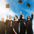 Happy multi ethnic group of graduated young students throwing hats in the air — Stok fotoğraf