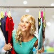 Smiling blond woman choosing clothes on a rack in a shopping mall — Stock Photo #45809019