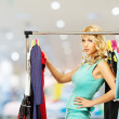 Smiling blond woman choosing clothes on a rack in a shopping mall   — Stock Photo #45809047