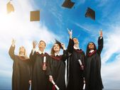 Happy multi ethnic group of graduated young students throwing hats in the air — Stock Photo