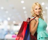 Smiling young blond woman with shopping bags in clothing store  — Stock Photo