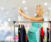 Smiling blond woman choosing clothes on a rack in a shopping mall — Stock Photo