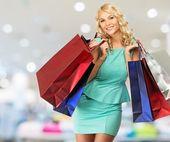 улыбается молодая блондинка женщина с сумки в магазине одежды — Стоковое фото
