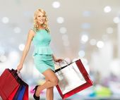 Smiling young blond woman with shopping bags in clothing store  — Stockfoto