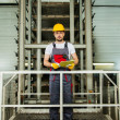 Man in a safety hat taking notes on a factory — Stock Photo