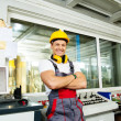 Happy worker wearing safety hat in a factory control room — Stock Photo