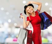 Smiling young blond woman with shopping bags in shop interior  — Stock Photo