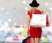 Mujer rubia con sombrero y vestido rojo con bolsas en el interior de la tienda — Foto de Stock