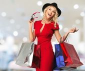 Smiling young blond woman with shopping bags in shop interior  — ストック写真