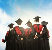 Group of graduated young students in black mantles against blue sky — Stock Photo