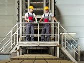 Two men in a safety hats on a factory   — Stock Photo