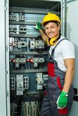 Cheerful electrician in a safety hat on a factory — Stock Photo