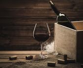 Bottle and glass of red wine on a wooden table  — Stock Photo